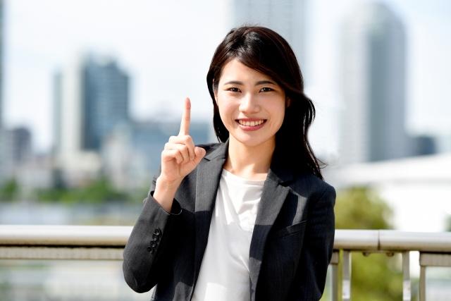 指さしをするスーツ姿の若い女性
