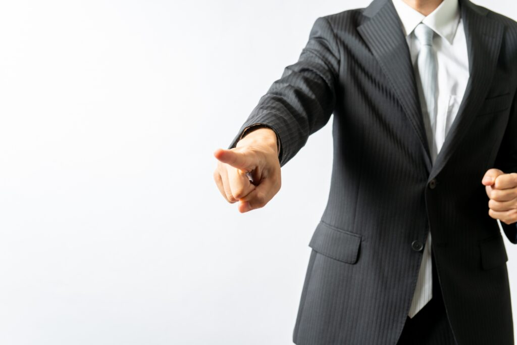 指さしをするスーツ姿の男性