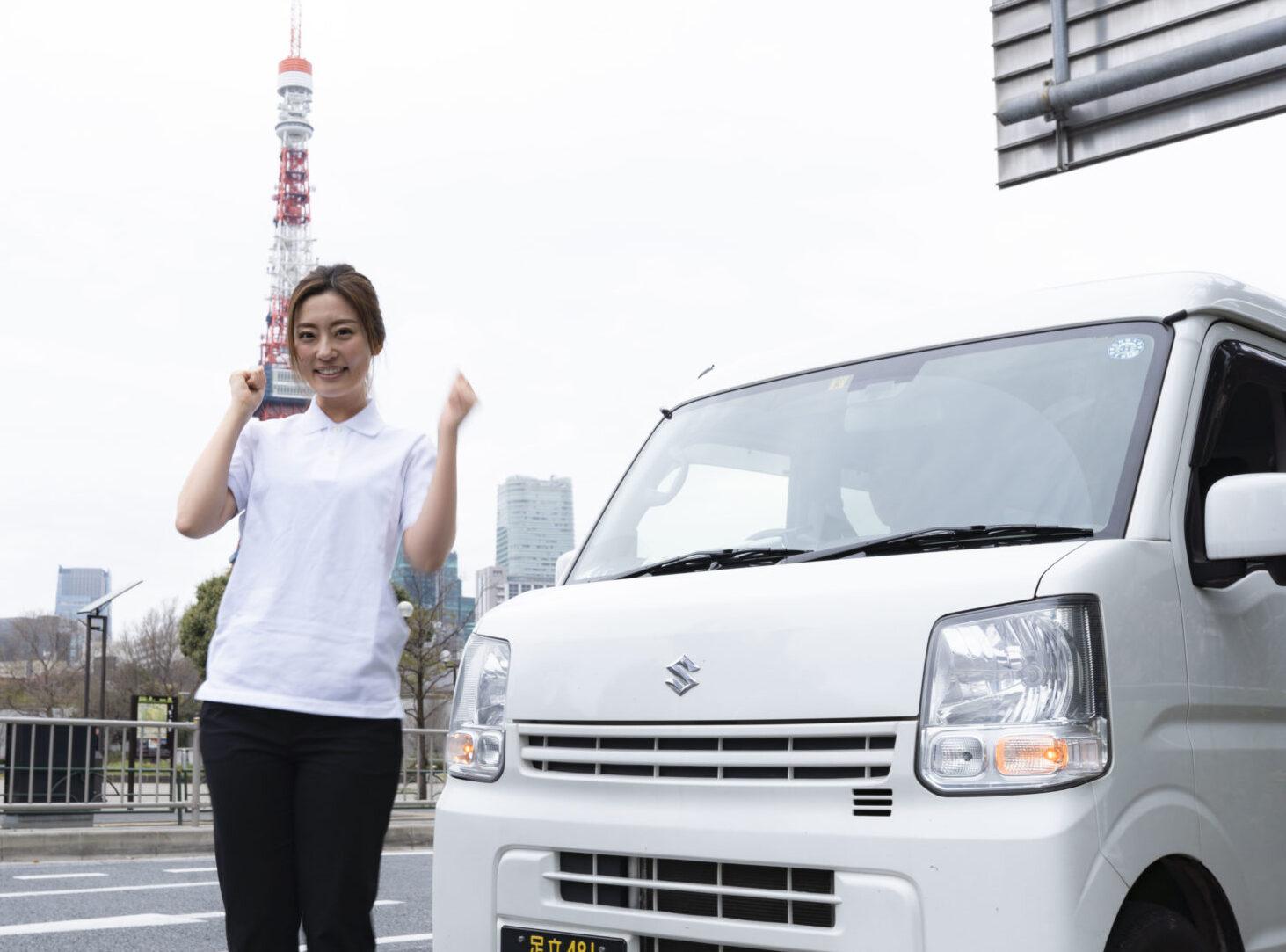 軽貨物車両の前でポーズを取る若い女性
