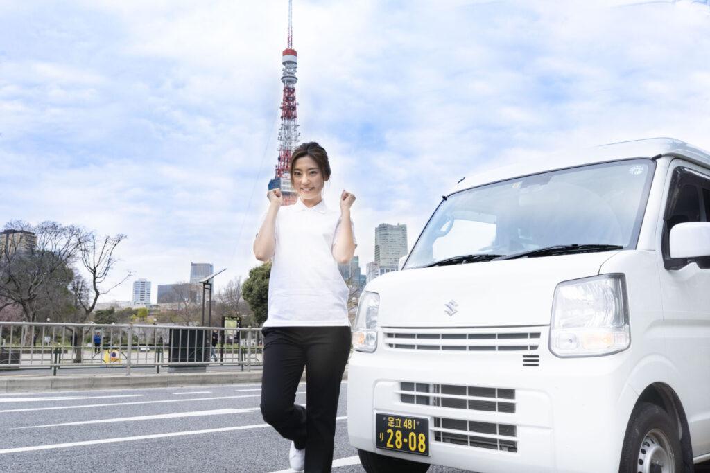 東京タワーをバックにポーズを取る若い女性ドライバー