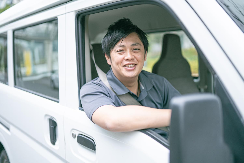 運転席からポーズを取る男性ドライバー