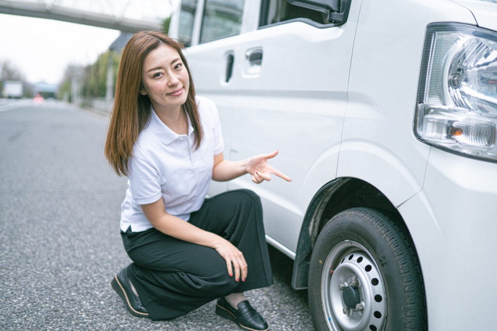 軽貨物車両のタイヤを指さす若い女性ドライバー