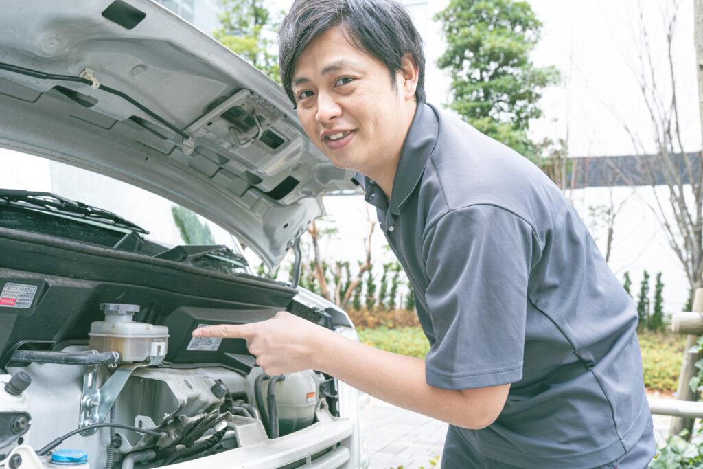 車のエンジンを指さす男性