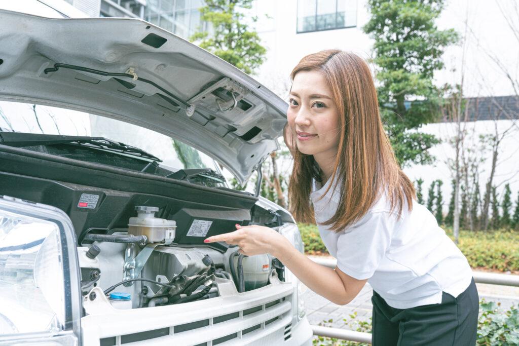 車のエンジンを指さす若い女性