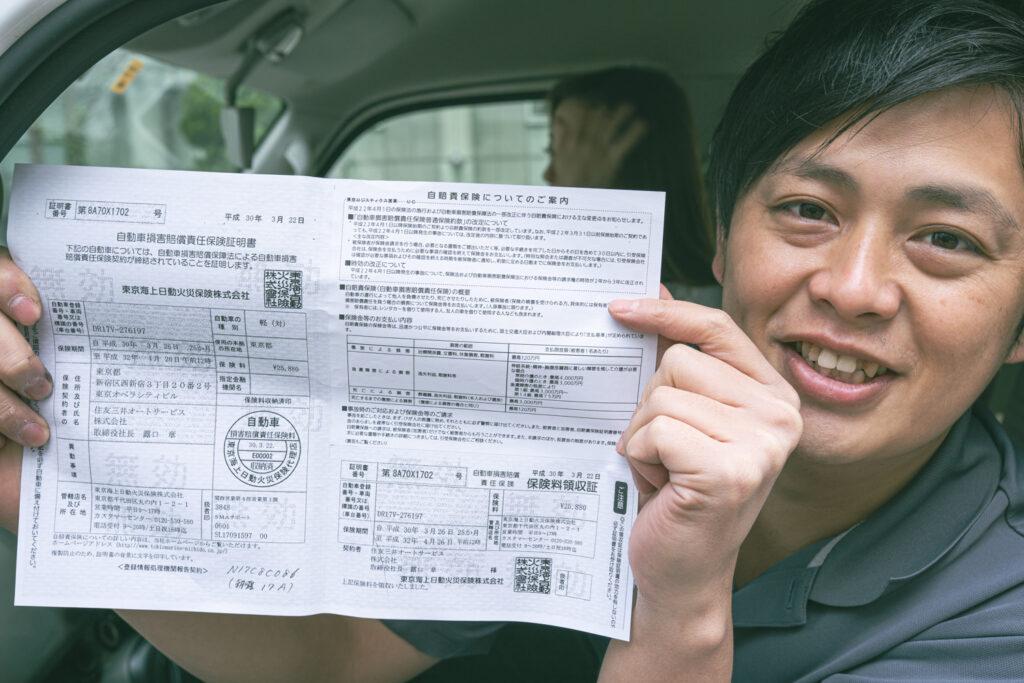 自動車保険書を手にする男性