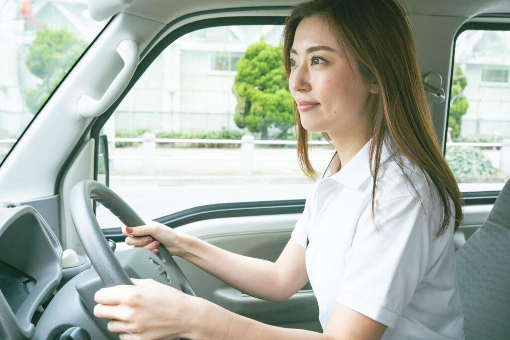 運転する若い軽貨物女性ドライバー