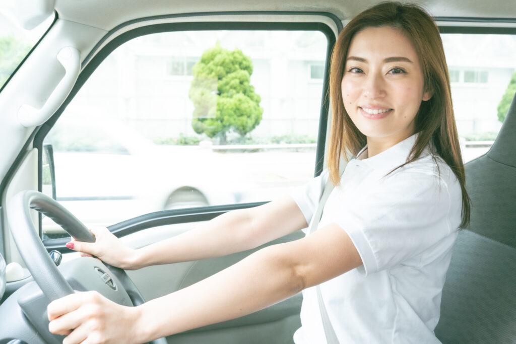 運転席でポーズを取る若い女性ドライバー
