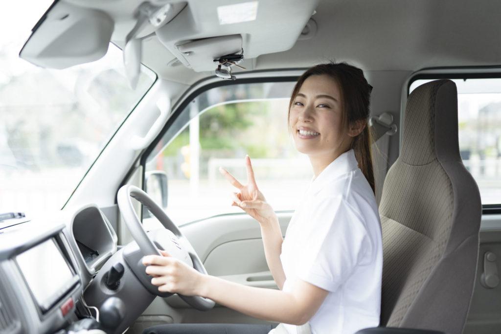 車両内でピースをする若い女性ドライバー