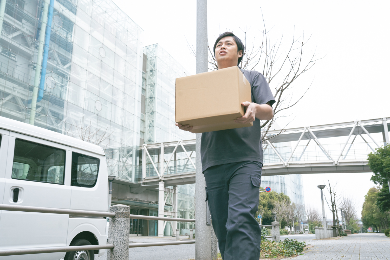荷物を運ぶ男性の軽貨物ドライバー