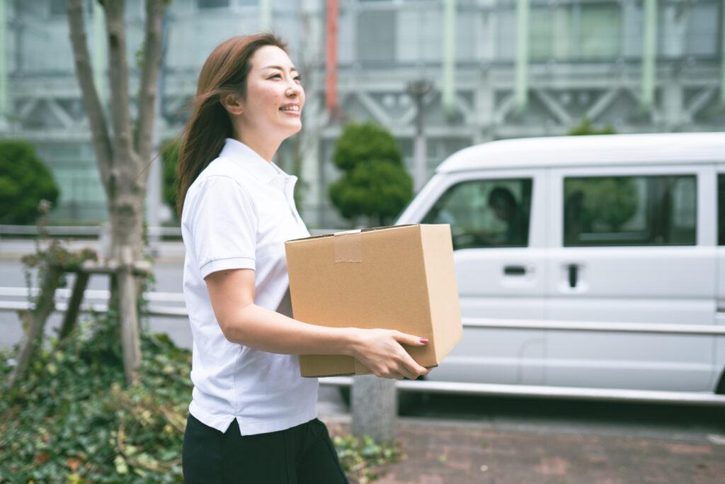 荷物を運ぶ若い軽貨物女性ドライバー