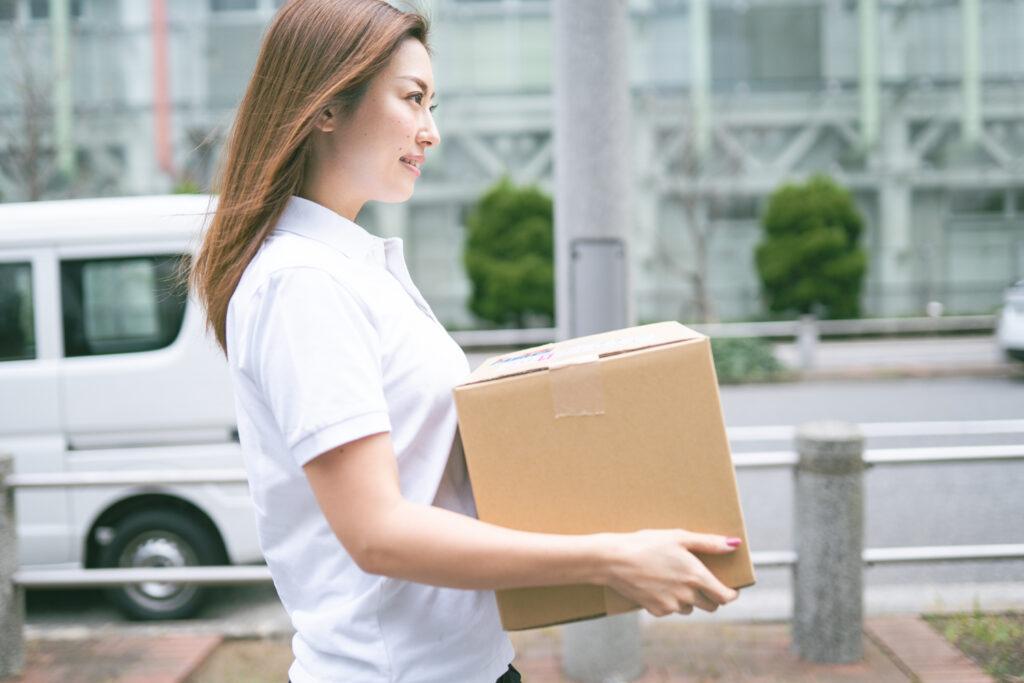 荷物を運ぶ若い女性配達員