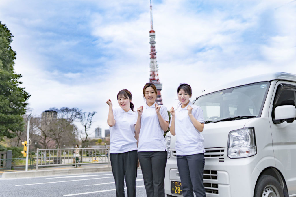 東京タワーをバックにポーズを取る三人の若い女性