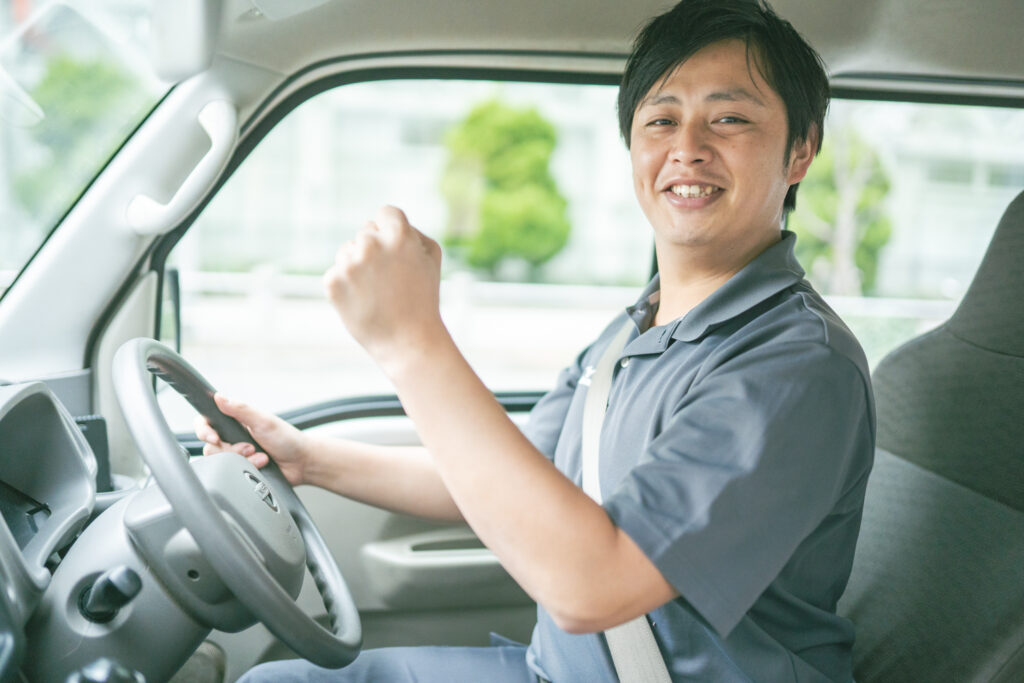 う運転席でガッツポーズをする男性