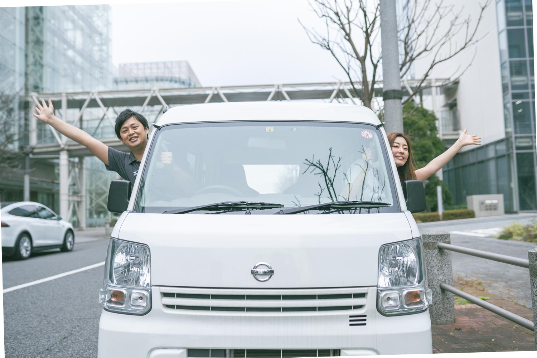 軽貨物車両の窓から身を乗り出してポーズを取る男女