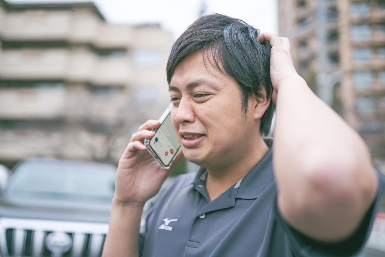 電話で謝っている男性ドライバー