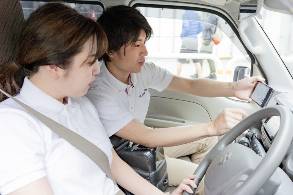 ナビを確認する車内の二人の若い男女