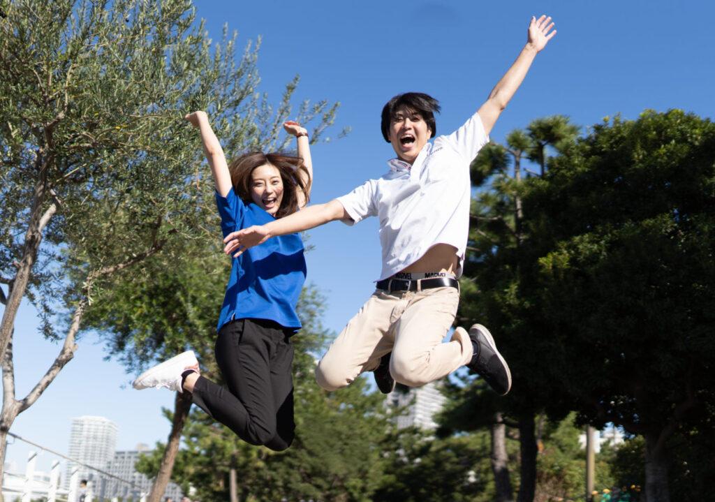 高くジャンプする若い男女