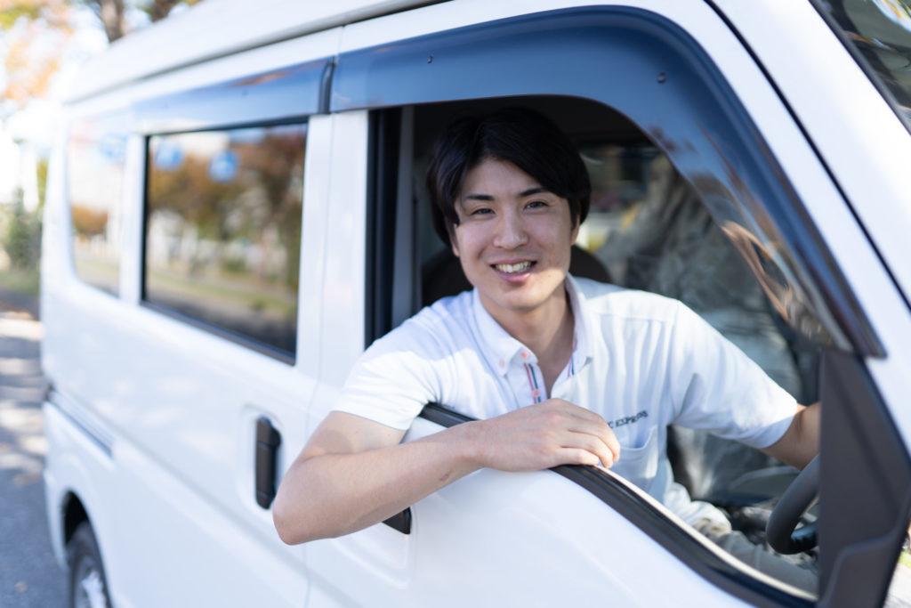 軽貨物車に乗ってポーズを取る若い男性