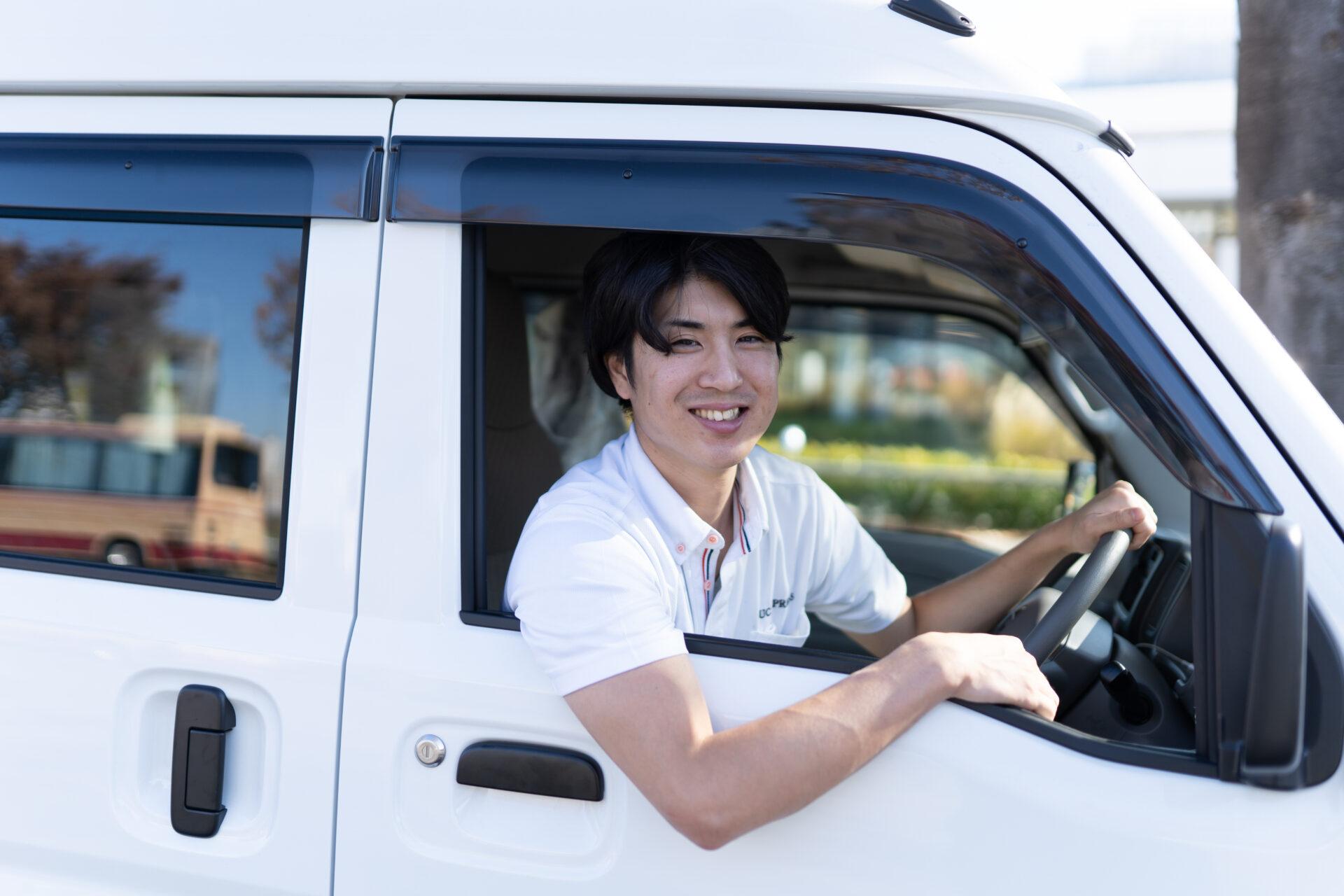 軽貨物車両の運転席でポーズを取る若い男性ドライバー