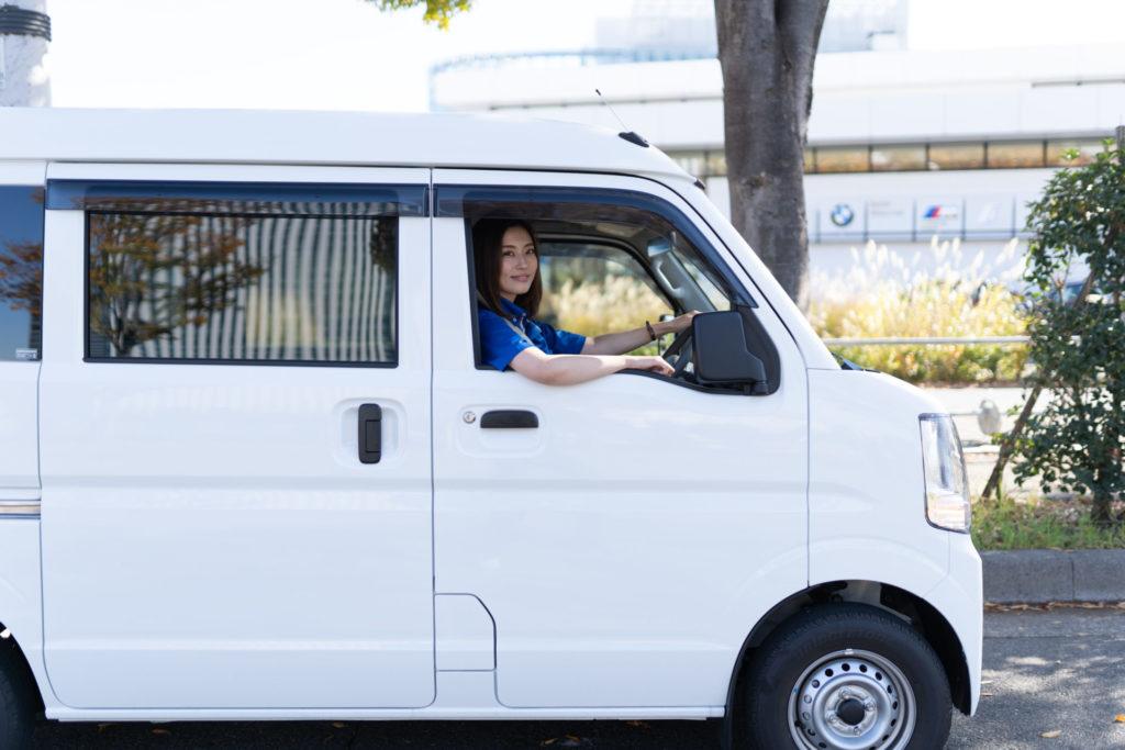 軽貨物車両を運転する若い女性ドライバー
