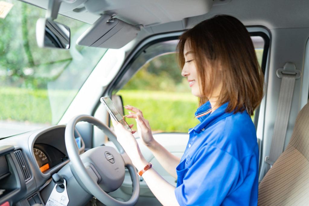 社内で携帯を見る若い女性ドライバー