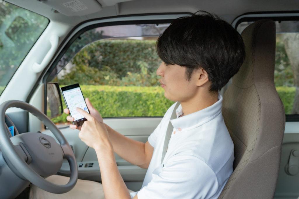 車内で携帯を見る若い男性ドライバー