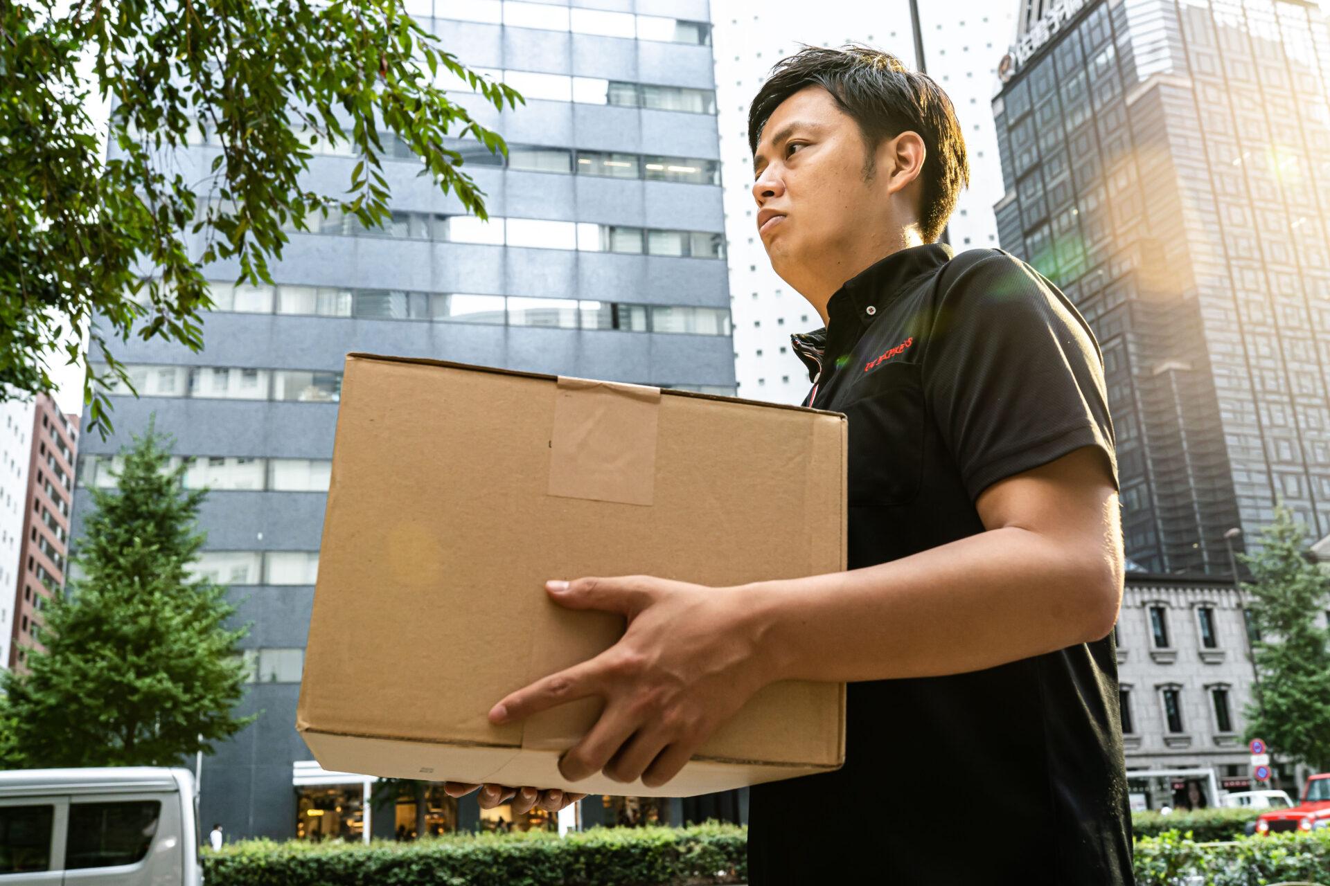 荷物を運ぶ軽貨物男性ドライバー