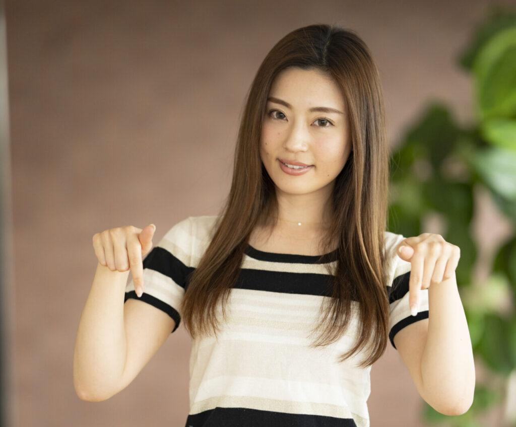 両手の人差し指を下に向けてダウンのポーズを取る若い女性