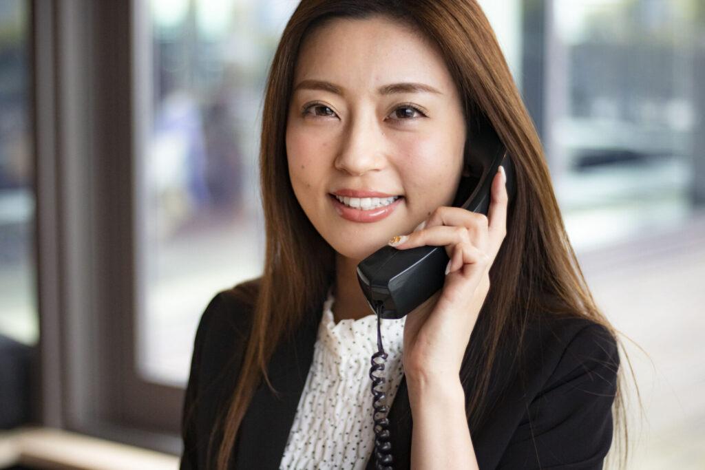 電話応対するスーツ姿の若い女性